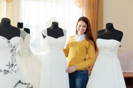 bridal salon: Smiling woman chooses  wedding dress in bridal salon