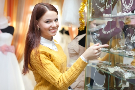 woman chooses bridal accessories in wedding boutique photo