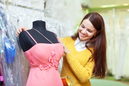 evening gown: Smiling woman chooses evening gown at clothing store