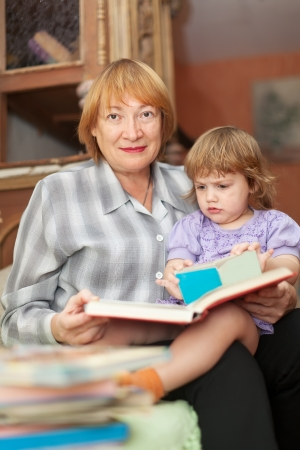Mature woman and baby girl reads book in home Stock Photo - 17058439