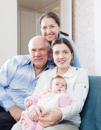Portrait of happy grandparents with daughter and granddaughter in home interior   photo