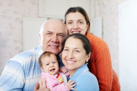 Portrait of cheerful grandparents with daughter and granddaughter in home inter together Stock Photo - 17067239