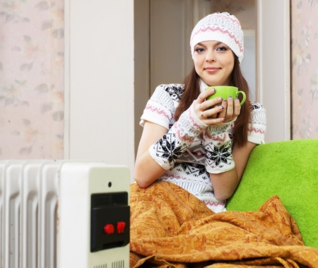 calorifer:  smiling woman in hat with cup near oil heater at home