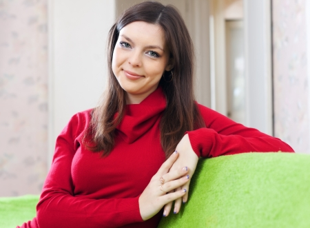 portrait of brunette smiling girl in red at home interior Stock Photo - 17076278