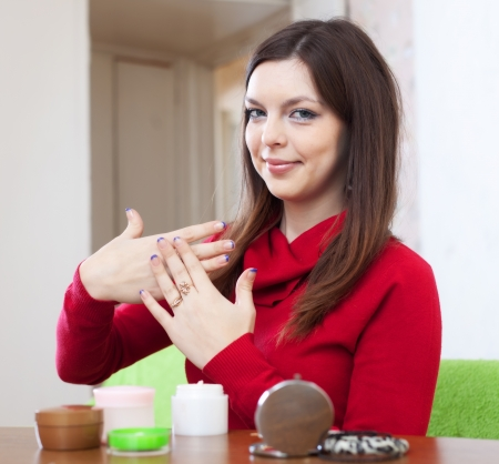 Pretty young woman puts cream on hands at home Stock Photo - 17076248
