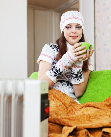 woman relaxing with cup near heater at home in winter Stock Photo