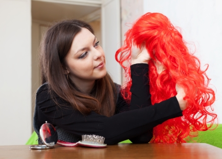 Young brunette woman with red wig at home Stock Photo - 17076288