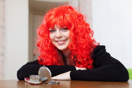 periwig: Smiling woman in red wig at home