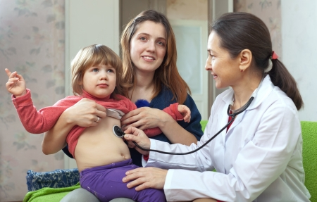children's doctor: mature childrens doctor examining 2 years child with  stethoscope. Focus of mother