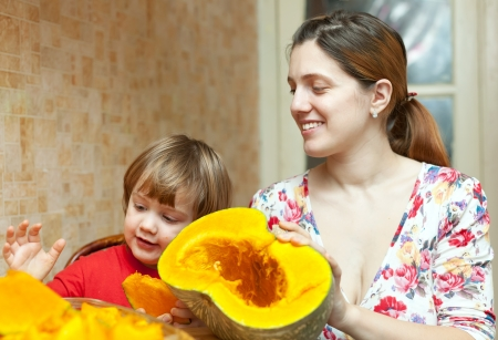 Happy mother with child cooks pumpkin  in  kitchen at her home Stock Photo - 17100394