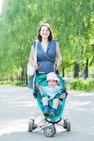 young mother with stroller is walking in summer park photo