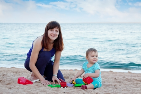 Happy mother with  toddler plays on sand beach photo