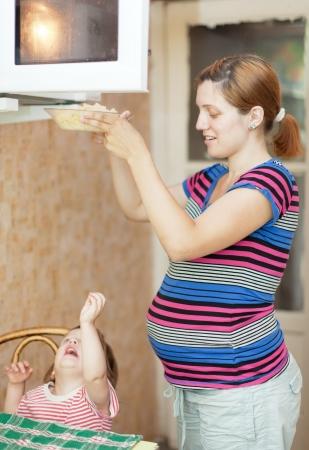 microwave oven: mujer embarazada con cocina con horno microondas infantil Foto de archivo