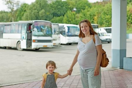 motorbus: Mujer embarazada feliz con el ni�o en la estaci�n de autobuses Foto de archivo