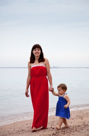 mother with  toddler walking  on sand beach photo