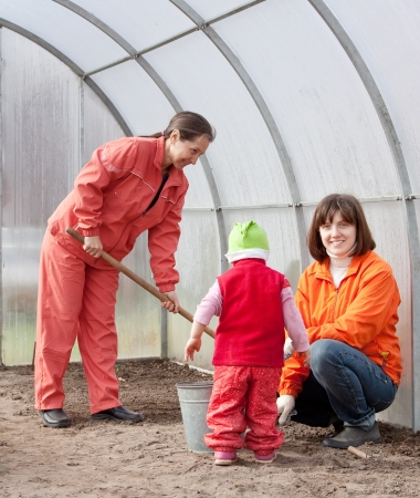 Happy family sows seeds in soil at greenhouse photo