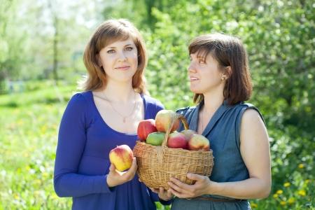 Happy girls with apples harvest in garden Stock Photo - 17123543