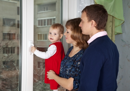 Parents with a child looking out the window in home Stock Photo - 17123534
