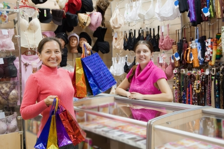Buyer  and salesman  with purchases at  counter in underwear shop photo