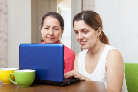 adult daughter helps mature mother using laptop in home Stock Photo - 17155396