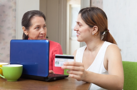 adult daughter helps mature mother shopping online with laptop and credit card  in living room at home photo