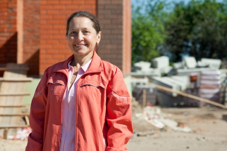 homeownership: Happy  mature woman  against  construction work
