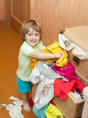 hellion:  Baby girl  chooses dress in parents wardrobe  Stock Photo