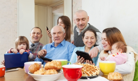 Happy family of three generations or group of friends with electronic devices  photo