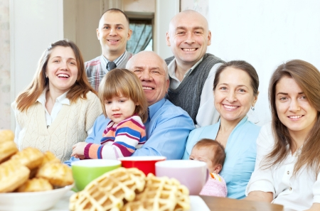 large joyful three generations family sits  in home photo