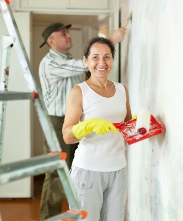 priming brush: Smiling woman and man makes repairs in home interior  Stock Photo