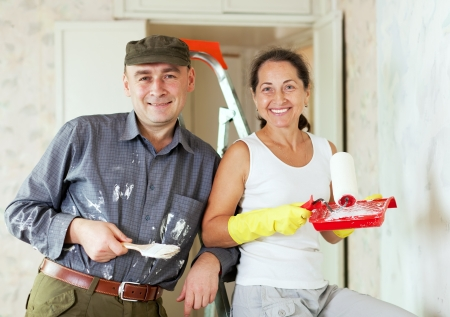 Happy woman and man makes repairs in home interior together photo