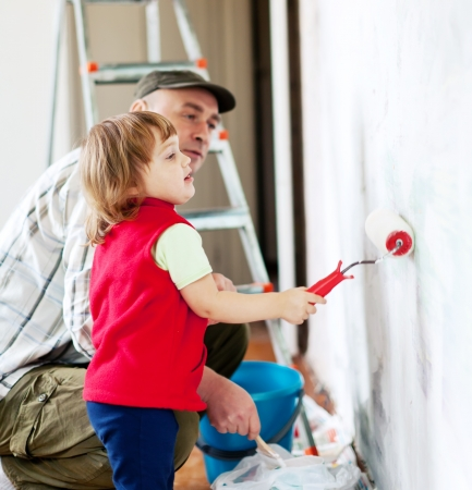 child  with father paints wall  at home Stock Photo - 17181301