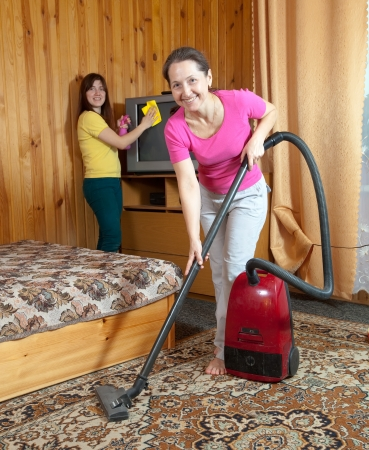 Women cleaning with vacuum cleaner in home