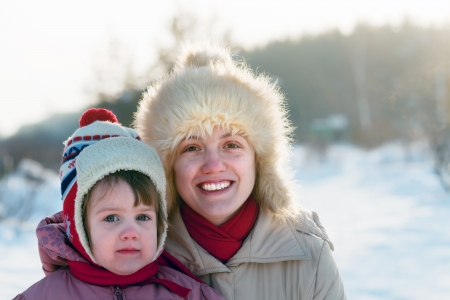 Portrait of happy mother with child in winter park photo