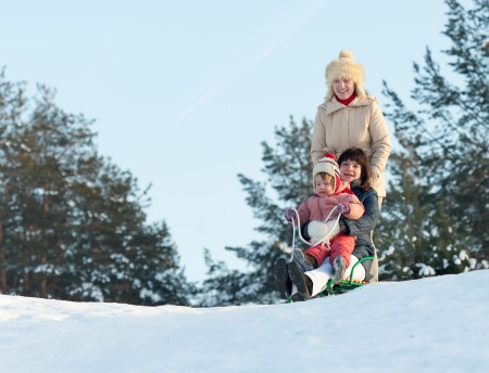 Women with child doing downhill on sleigh in winter park photo