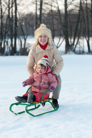 Happy 2 years child on sled with mother in winter park photo