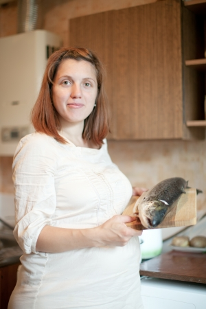 gravida: pregnant woman with salmon in the kitchen