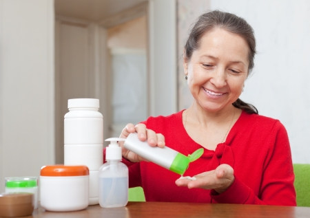 smiing: Smiing mature woman in red uses cosmetic cream in home interior Stock Photo