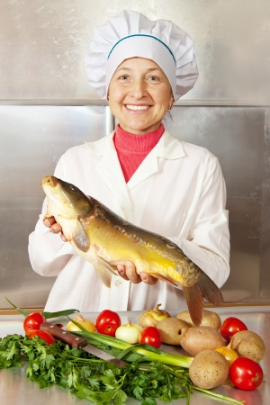 Cook woman with carp fish in kitchen photo