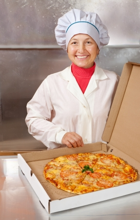 female cook with fresh  pizza in box at kitchen photo