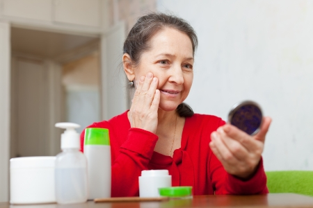 mature woman stares for facial wrinkles in mirror  photo