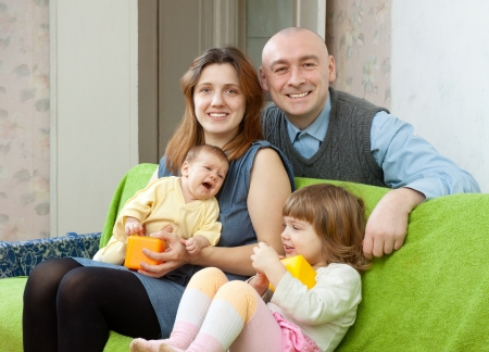 family of four together with newborn baby on sofa at home photo