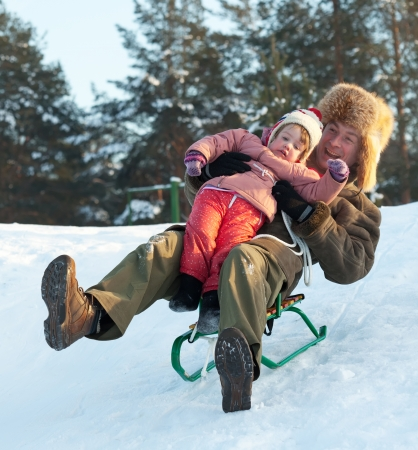 Man with child sliding on sleds downhill in winter park photo