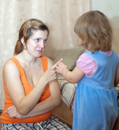 scold: Mother berates  child in interior. Focus on woman only Stock Photo