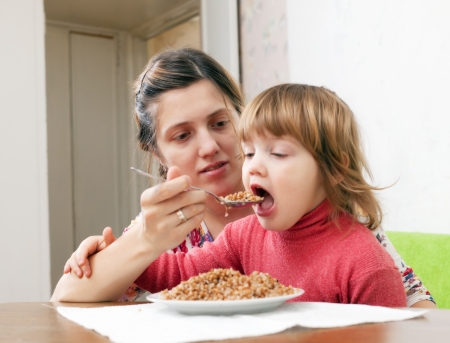 Mother feeding her 2 years child at home. Focus on woman photo
