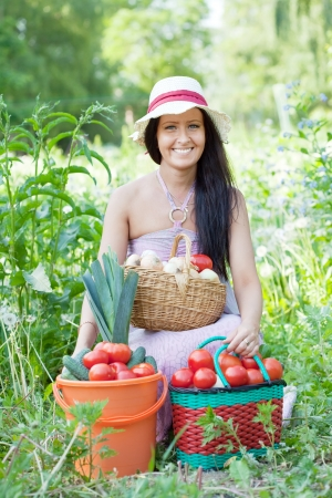 Happy woman with basket of harvested vegetables in garden photo