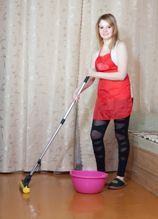 woman washes the floor with mop in the living room photo