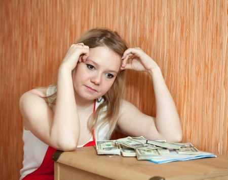 thinks: The woman thinks about the financial issue at home Stock Photo