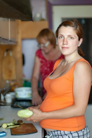 gravida: Two women cooks with vegetables in  kitchen