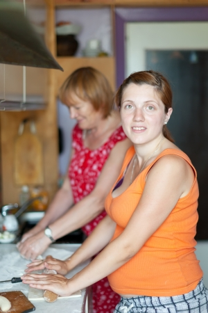 gravida: Two women makes pie with fillings in  kitchen